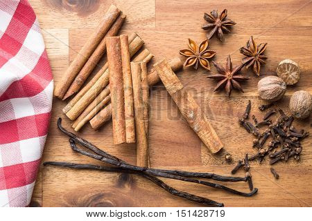 Vanilla, cinnamon, clove, nutmeg and anise star on wooden table. Top view.
