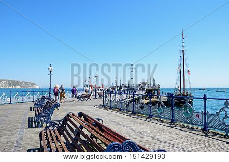 SWANAGE, UNITED KINGDOM - JULY 19, 2016 - View along the Victorian pier with tourists enjoying the Summer sunshine Swanage Dorset England UK Western Europe, July 19, 2016.