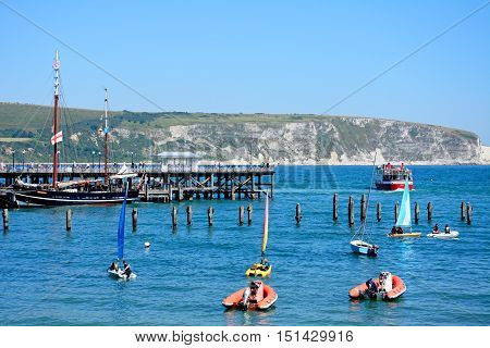 SWANAGE, UNITED KINGDOM - JULY 19, 2016 - The Moonfleet tallship moored alongside the Victorian pier with dinghies and a ferry in the bay Swanage Dorset England UK Western Europe, July 19, 2016.