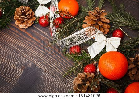 Red Christmas balls fir branches and tangerines on a wooden table