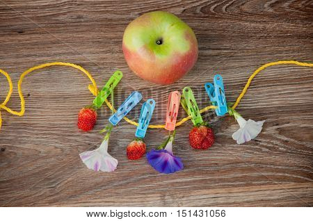 Red strawberry and petunia flowers on yellow rope with colorful clothespins near big apple on brown wooden background. Top view