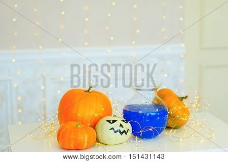 Table with Halloween pumpkins and bottle of potion