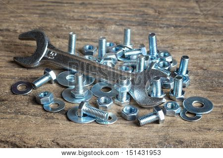 wrench and nuts and bolts on wooden table