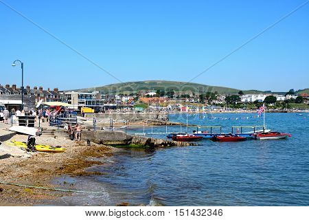 SWANAGE, UNITED KINGDOM - JULY 19, 2016 - Boats moored along a small jetty with views along the beach with the town to the rear Swanage Dorset England UK Western Europe, July 19, 2016.