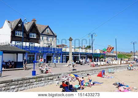 SWANAGE, UNITED KINGDOM - JULY 19, 2016 - View along the beach with holidaymakers enjoying the setting and an amusement arcade to the rear Swanage Dorset England UK Western Europe, July 19, 2016.