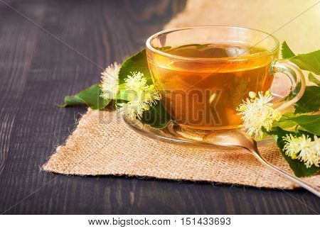 Linden tea on a wooden table in a glass cup. Flower tea herbal medicine.