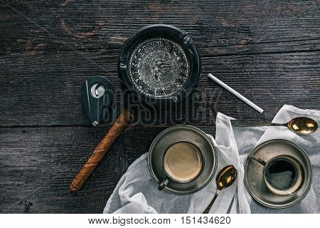 Metal vintage cups of coffee, cigar, cutter, slim sigarette and ashtray on the wooden table. Flat lay