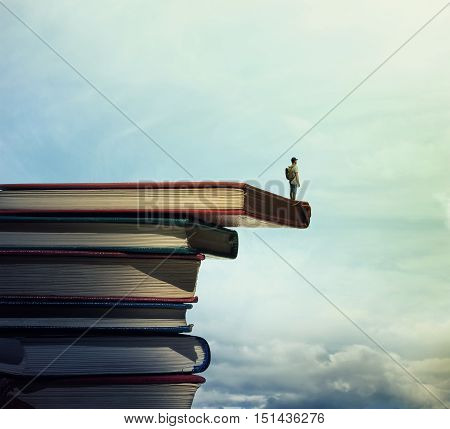 Young boy with a bag on his back stand on a stack of books looking far at horizon. In search of knowlegde concept.