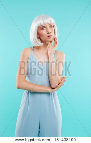Stylish pretty young woman in blonde wig standing