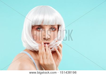 Portrait of amazed pretty young woman in blonde wig