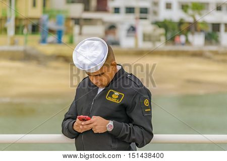 SALINAS, ECUADOR, OCTOBER - 2015 - Officer watching and concentrated on his chatting cellphone at Salinas Ecuador