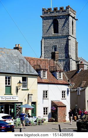 WAREHAM, UNITED KINGDOM - JULY 19, 2016 - Lady St Mary parish church tower seen above shop buildings Wareham Dorset England UK Western Europe, July 19, 2016.
