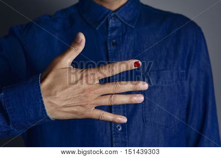 closeup of the hands of a young man with one of his fingernails polished in red, in support of children victim of violence