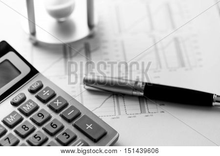 Hourglass and Calculator on Business Graphs and Charts