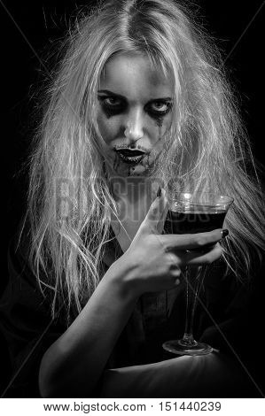 blond witch with bloody glass on black background, monochrome