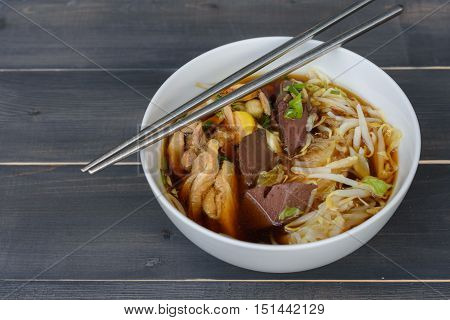 noodle soup with chopsticks in bowl on a wooden table Thai local food