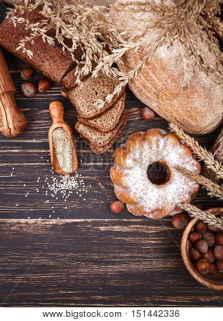 Fresh crispy breads baking of loaf and sweet donut on old wooden plate in rustic style
