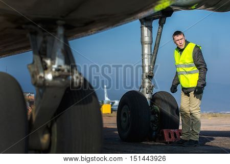 Male engineer checking airplane's chassis before flight