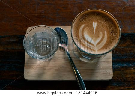hot fresh coffee in see through glass water glass on wooden tray and table silver spoon at coffee time / hot fresh coffee