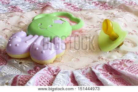 Set newborn baby toy teether and pacifier on the fabric for the background.