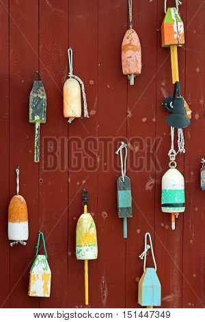 Colorful , wooden buoys hanging on a weathered building