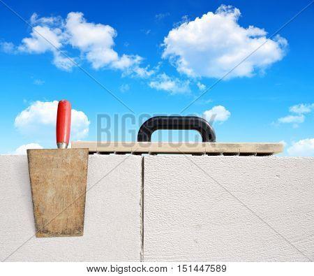 Masonry tools on brick wall. Bricklaying work.