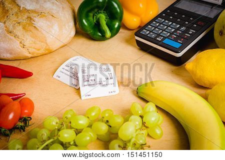 cash register and the bill on a wooden table with vegetables
