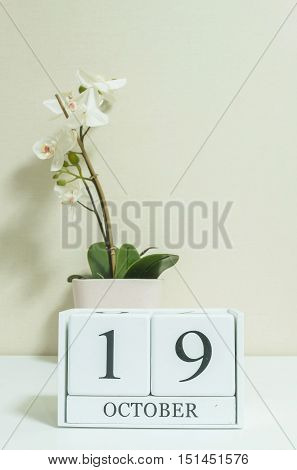 Closeup white wooden calendar with black 19 october word with white orchid flower on white wood desk and cream color wallpaper in room textured background view another more date in my portfolio