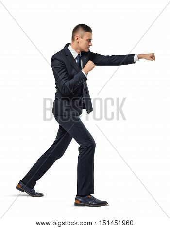 Businessman acting like he is punching someone on a white background. Facing challenges. Tough competition. Fighting spirit.