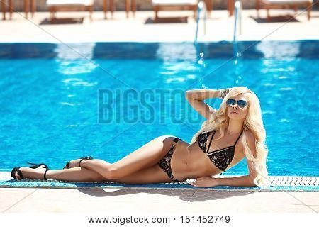 Beautiful Sexy Woman In Black Bikini, Blond Model With Sunglasses Tanned And Lying By The Blue Swimm