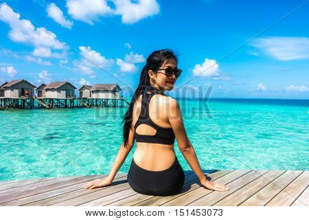 Portrait of happy young woman (fitness, bikini, perfect tanned body, healthy skin) at beautiful water villa at maldives island. Travel and Vacation. Freedom Concept. Outdoor shot