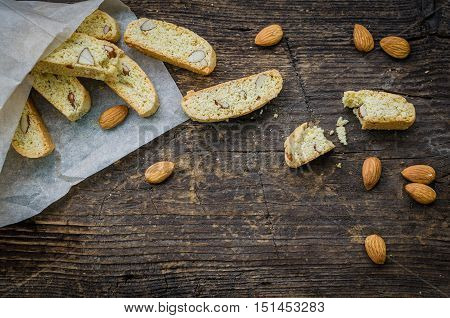 Italian cantuccini cookies with almond. Traditional italian almond cookies biscotti on old wooden background. Homemade Almond cookies with space for text on wooden table. Top view. Copy space.