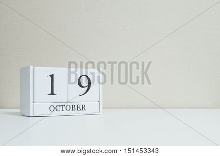 Closeup white wooden calendar with black 19 october word on blurred white wood desk and cream color wallpaper in room textured background with copy space view another more date in my portfolio