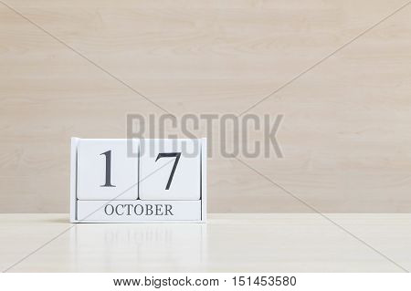 Closeup surface white wooden calendar with black 17 october word on blurred brown wood desk and wood wall textured background with copy space view another more date in my portfolio