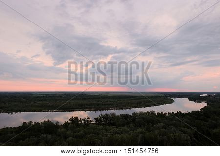 Cold dawn at the river. Summer landscape. Beautiful clouds and hills.