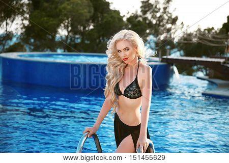 Beautiful Elegant Woman Model With Long Blonde Wavy Hair Style Wearing In Black Swimsuit  Posing In