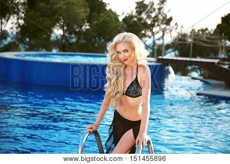 Long Wavy Hair. Beautiful Sexy Woman Model In Black Swimwear Posing In Blue Swimming Pool At Park. S