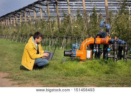 Engineer With Irrigation System In Orchard