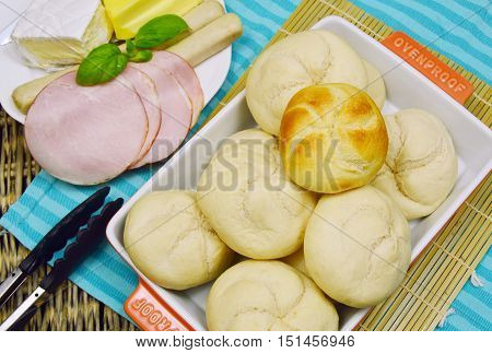 Kaiser roll wait for baking with sausage cheese ham and butter. Kaisersemmel is German name, Kaiser roll is English name