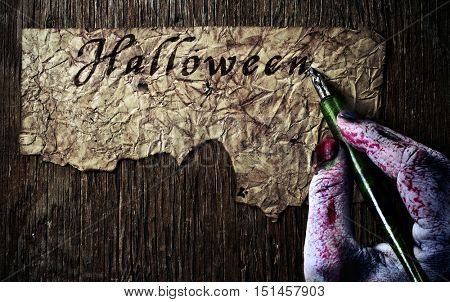 closeup of the scary hand of an undead man writing the word Halloween with a nib pen in a yellowish and wrinkled piece of paper, on a rustic wooden table