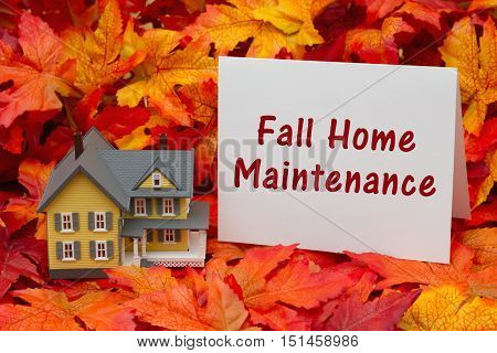 Home maintenance for the fall season Some fall leaves and yellow and gray house and greeting card with text Fall Home Maintenance