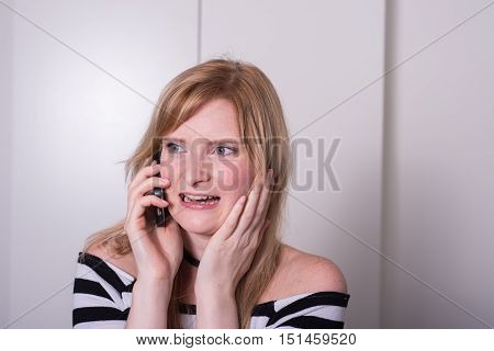 beautiful blonde woman is very upset during a phone call
