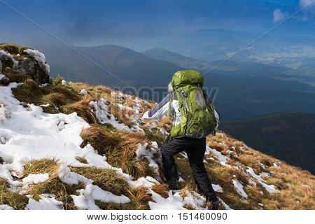 Woman Traveler with Backpack hiking in the Mountains Female hiker standing on mountain on hiking trek. Side view of woman in warm clothing carrying backpack.