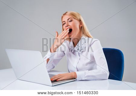 Young businesswoman working at laptop computer. she tired after work, yawns