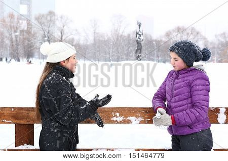 two teenager girl in knitted woolen hat and down overall and jacket on the skating ring talk on smile on the snowy white background