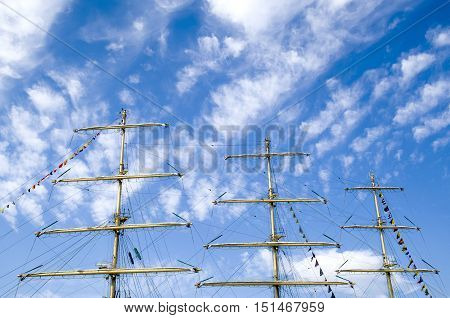 Three masts of a sailing ship in cloudy sky
