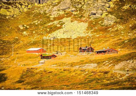 lost red cottages in rough norwegian landscape during autumn