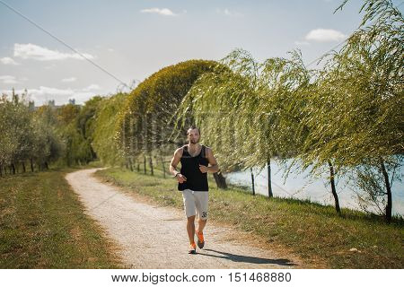 Energetic Young Man Do Exercises Outdoors In Park To Keep Their