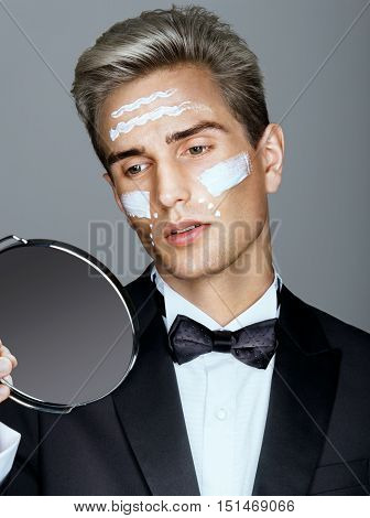 Fashion man with cosmetic cream treatment on his face looking in the mirror. Portrait of very handsome man in elegant suit. Skin care concept