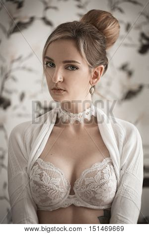 Beautiful sexy blonde perfect slim body shape natural make-up covers one eye fashion underwear. Sensual woman posing in lingerie. Portrait of girl in white lace brassiere.